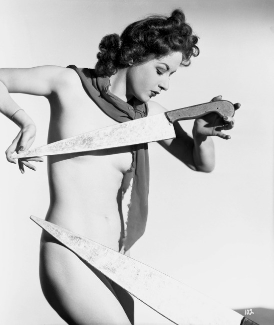 Maurice Seymour- nude model posing with a large, oversized knife, 1930s