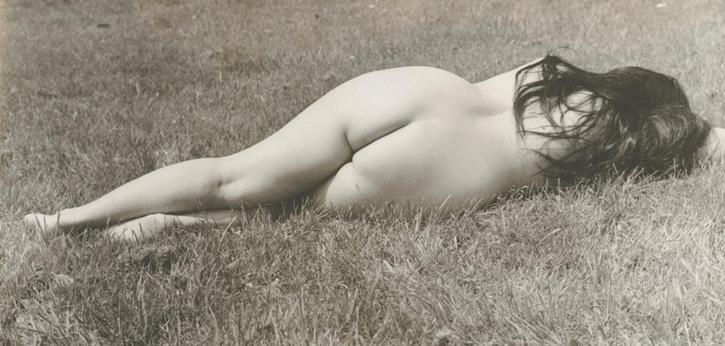 Josef Breitenbach-female nude with long dark hair, lying face-down on grass, full length with feet at left, 1961
