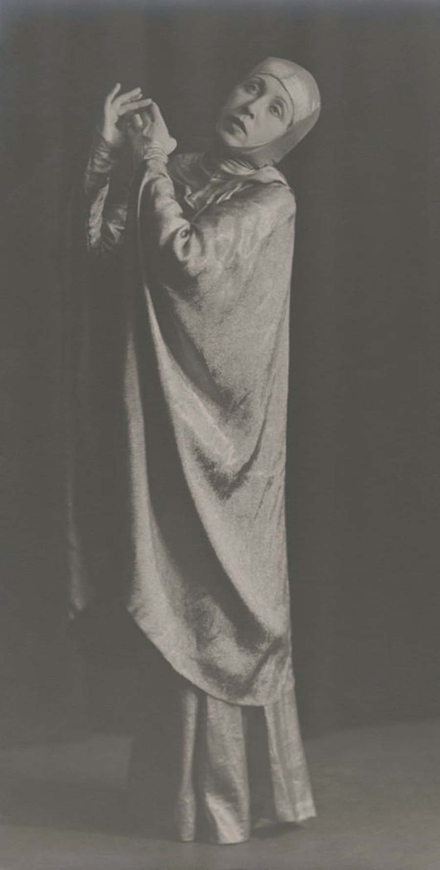 Josef Breitenbach-woman in costume of shiny material with cape and hood, 1930s
