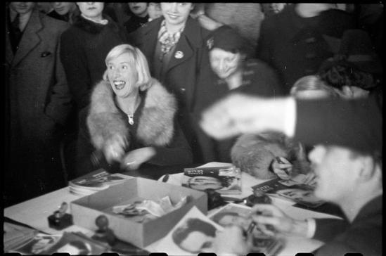 Roger Parry - Suzy Solidor assise entourée d'admirateurs lors d'une seance de dédicaces, 1940