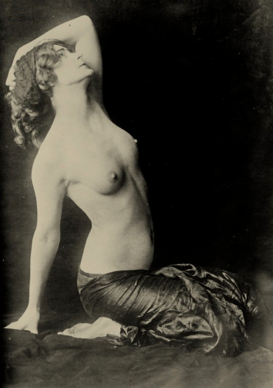 Dancer Adorée Villany, photoportrait, seated on ground, topless, right arm behind her with hand on ground, left arm raised above her head, bent at elbow., probably, 1910s