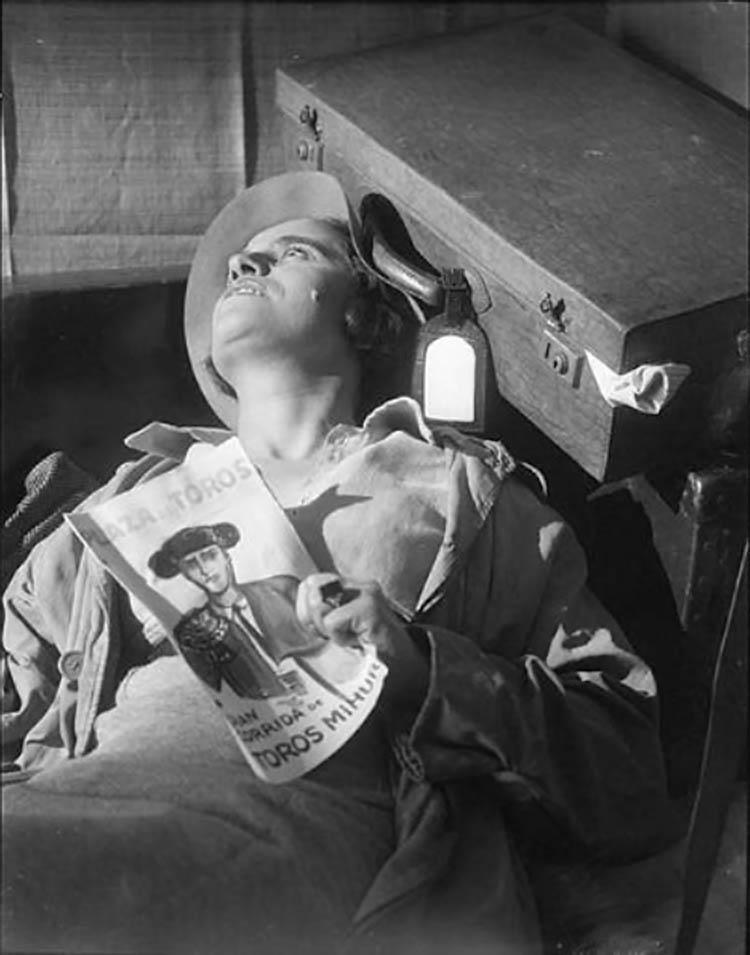 Roger Parry- Une femme étendue sur le dos, les yeux ouverts, la tête contre une valise et une revue de tauromachie dans une main1933