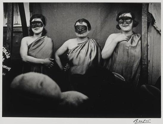Brassaï- Trois femmes masquées  sur l'estrade, devant la baraque  Sa Majesté la femme   spectacle interdit aux moins de 16 ans, Boulevard St. Jacques, Paris 1931