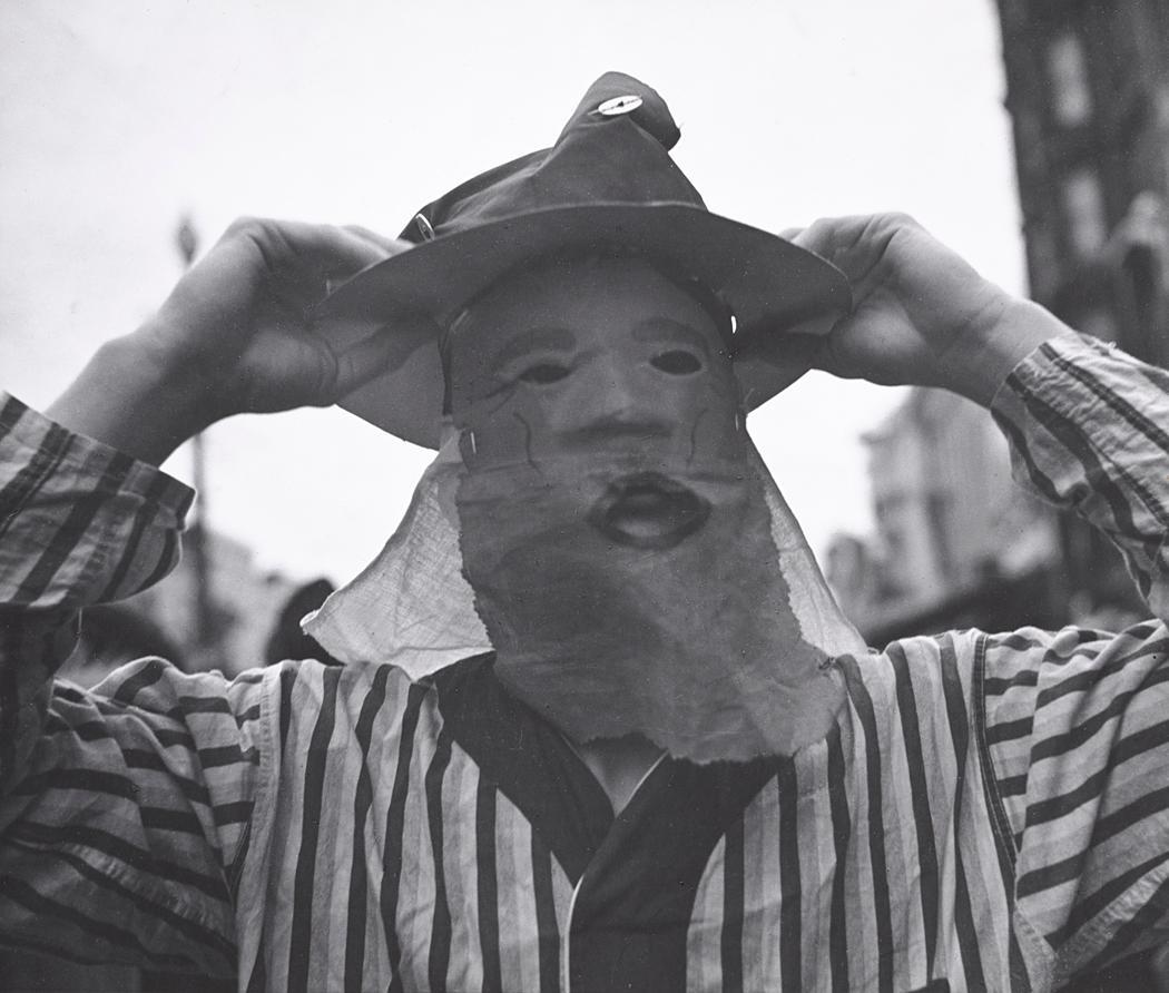 John Gutmann-Man Placing Hat Over Mask, Mardi Gras, New Orleans, 1937
