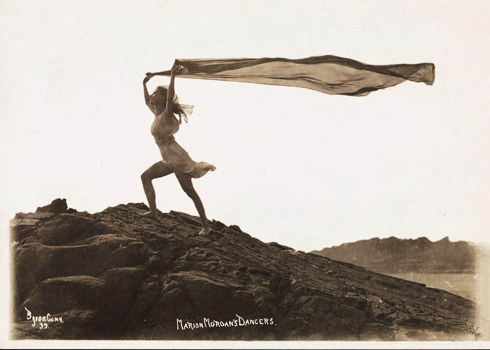 Byron Company - One of Marion Morgan's dancers with a long, diaphanous scarf flowing in the sea breeze, posing on rock at the beach Rye, New York. 1920