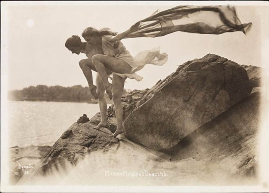 Byron Company - Two of Marion Morgan's dancers with flowing scarf, posing on rocks at the beach Rye, New York. 1920